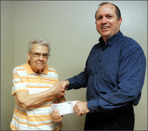"""Scot Daniels is shown presenting a check in the amount of $750 to the Nance County Foundation. Accepting the donation is Foundation representative Donna Bishop. The donation was given to the Foundation by Scot and Trish Daniels, owners of Scot Daniels State Farm Insurance of Albion and Fullerton. """"These foundations are valuable,"""" Scot noted.  """"Without these Foundations, projects do not get completed."""" Scot and Trish's name will appear on the plaque, now on display at the Fullerton National Bank. If you wish to have more information on the Foundation, contact Joe Wegner, president, or Tony Shotkoski, vice-president of the organization."""